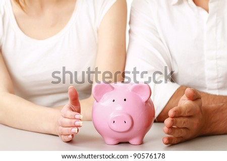 Young woman and man with piggy bank (money box), isolated on white background