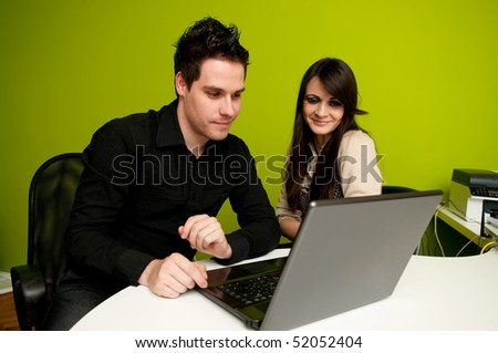 Young woman and man working on laptop computer smiling - stock photo