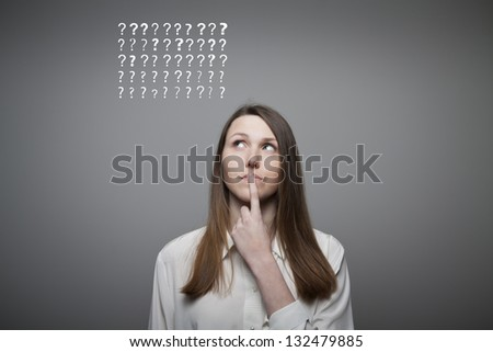 Young woman and many question marks above head - stock photo