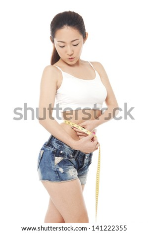 Young woman and measure tape around her body - a studio shot