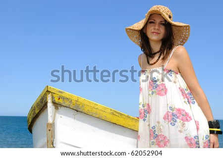 Young woman and rowboat an the north sea. - stock photo