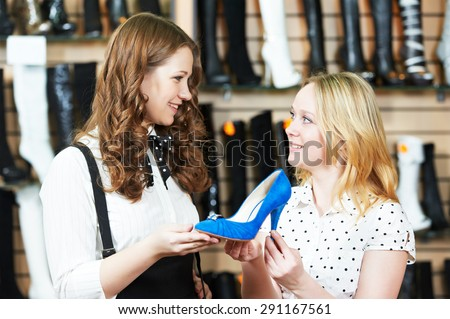 Young woman and seller assistant choosing footwear during shopping at shoe shop - stock photo