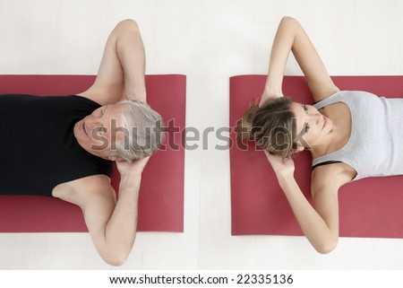 young woman and senior adult exercising in gym - stock photo