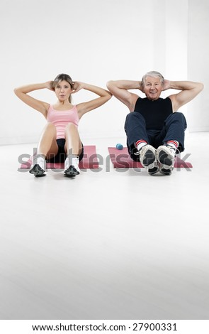 young woman and senior man doing abs in gym - stock photo