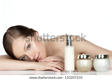 young woman and skincare products on white. Space for text. - stock photo