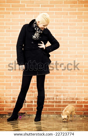 Young woman and small pet over urban background. - stock photo