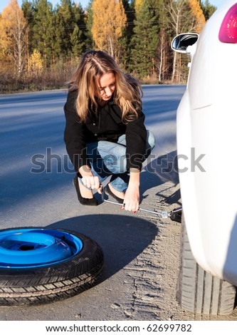 Young woman and the car with deflated wheel. - stock photo