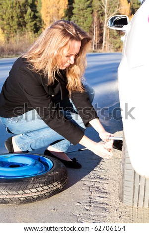 Young woman and the car with deflated wheel - stock photo