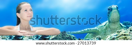 Young woman and turtle underwater - stock photo