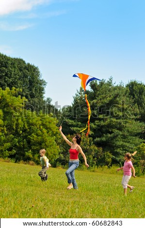 Young woman and two children flying a kite - stock photo