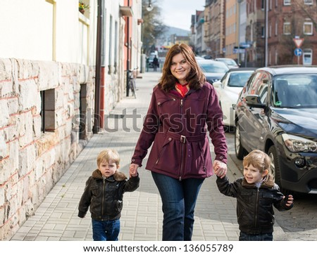 Young woman and two little boys walking through spring city, Germany