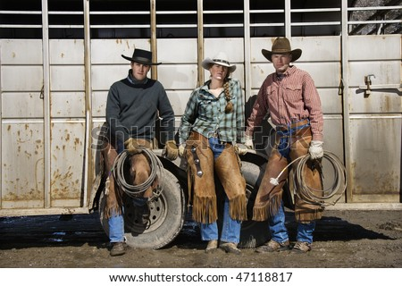 Young Woman and two men with lariats, leaning on the side of a livestock trailer. Horizontal shot. - stock photo