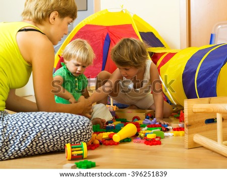 Young woman and two siblings together playing with  toys in  interior - stock photo