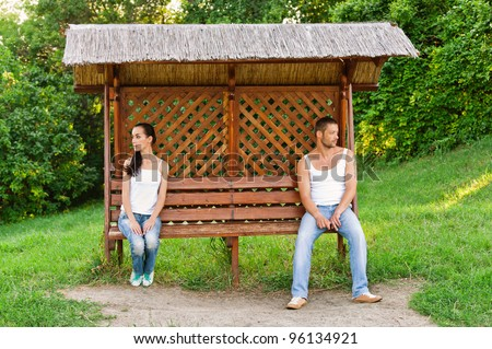 Young woman and young man sitting on opposite sides of bench in city park because they had falling out. - stock photo