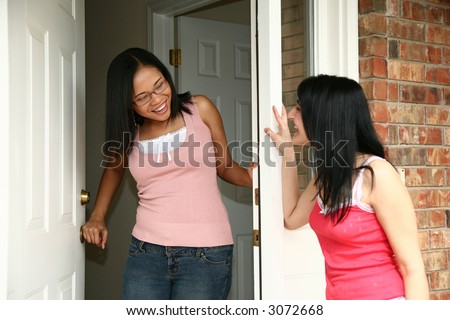 Young woman answering door for friend. - stock photo