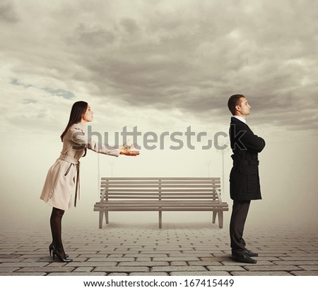young woman apologizing to man at outdoor - stock photo