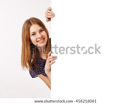 Young woman appear from the side of the billboard. - stock photo