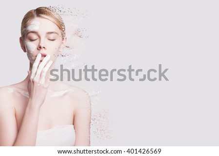 Young woman applies a mask to the face, she crumbles into small particles on a light background - stock photo