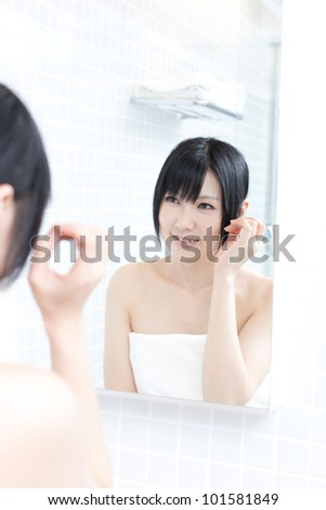 young woman applies makeup in front of a bathroom mirror - stock photo