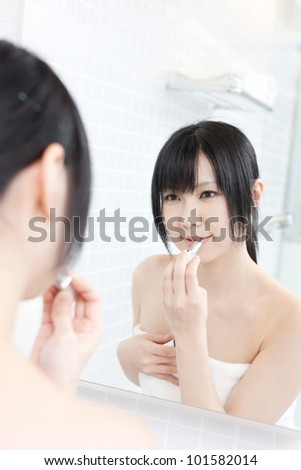 young woman applies makeup in front of a bathroom mirror