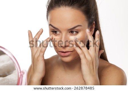 young woman apply different shades of liquid foundation on her face - stock photo