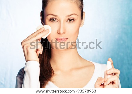 young woman apply foundation with sponge applicator, studio shot - stock photo