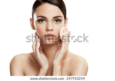 Young woman applying blusher on her face with powder puff, skin care concept / photo composition of brunette girl  - isolated on white background