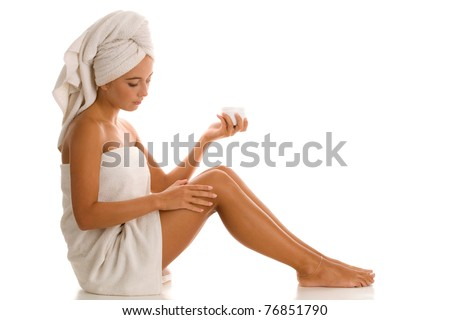 Young woman applying body lotion - stock photo
