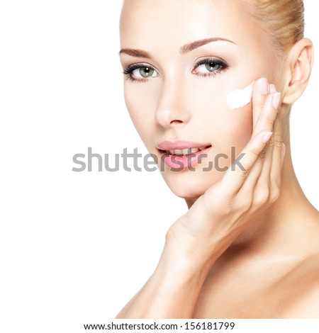 Young woman applying cosmetic  cream on a clean fresh face - stock photo