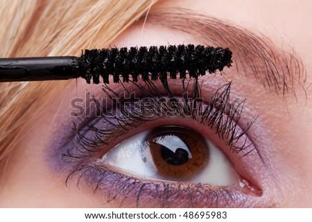 Young woman applying cosmetics on eyelashes closeup - stock photo