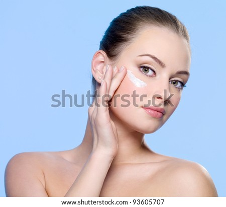 Young woman applying cream on her face - blue background
