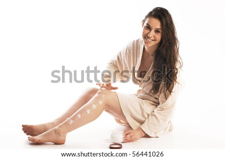 Young woman applying cream on her skin - stock photo