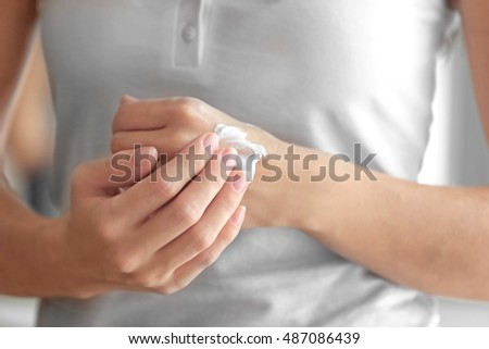 Young woman applying cream onto hands