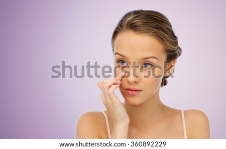 young woman applying cream to her face - stock photo