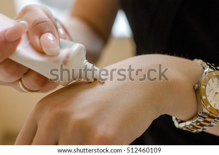 Young woman applying cream to her hand