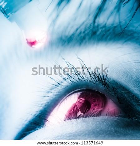 young woman applying eye drop - stock photo