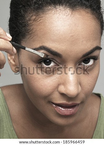 Young woman applying eye shadow
