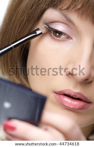 Young woman applying eye shadow, closeup - stock photo