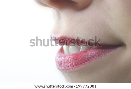 young woman applying lip balm isolated on a white  - stock photo