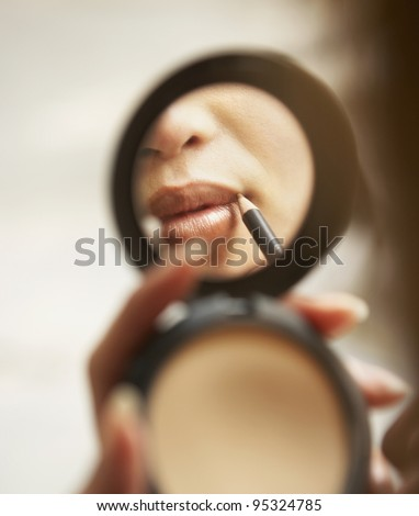 Young woman applying lip liner - stock photo