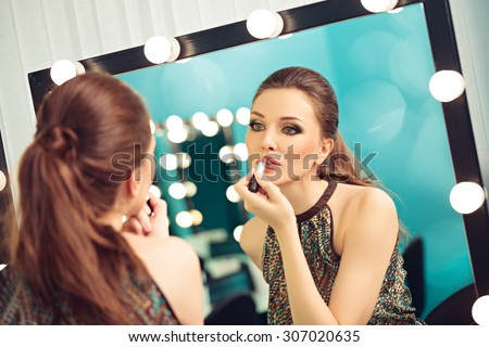 Young woman applying lipstick in front of a mirror