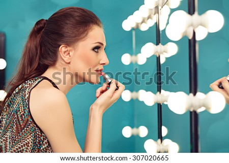 Young woman applying lipstick in front of a mirror - stock photo