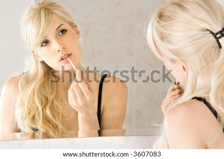 young woman applying lipstick in front of mirror - stock photo