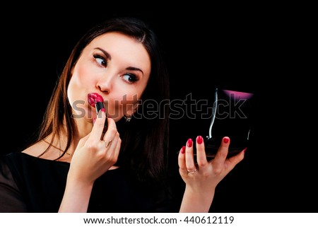 Young woman applying lipstick looking at mirror - stock photo