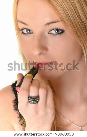 Young woman applying lipstick on white - stock photo