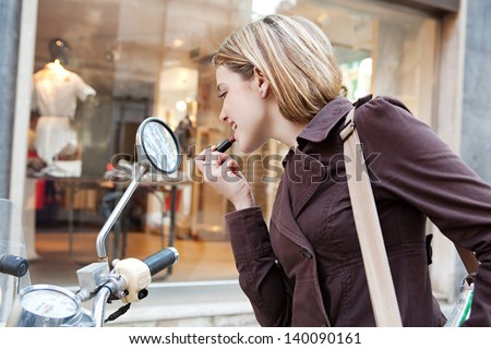 Young woman applying lipstick while in a shopping district street, using the reversing mirrors of her motorbike to put make up on. - stock photo