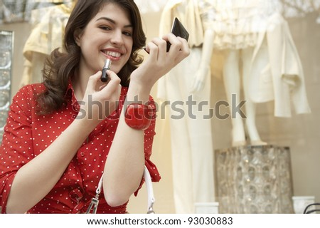 Young woman applying lipstick while sitting down by shop window. - stock photo