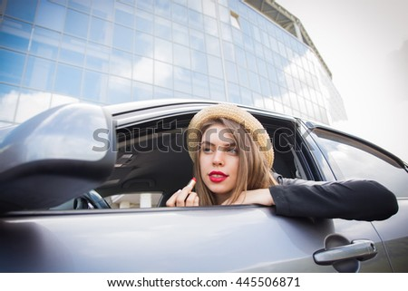 Young woman applying makeup while driving the car