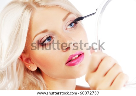 Young woman applying mascara looking at mirror