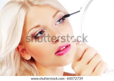 Young woman applying mascara looking at mirror - stock photo